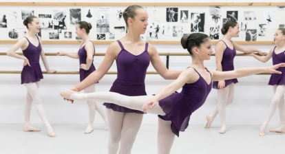 Young ballet dancers warming up and stretching