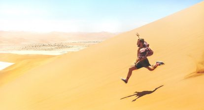 Man leaping down sand dune in desert